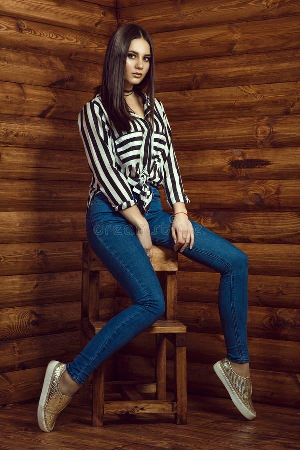 Portrait du jeune beau modèle aux cheveux foncés utilisant de hauts-waisted jeans maigres, chemise rayée, foulard et espadrilles  photos libres de droits