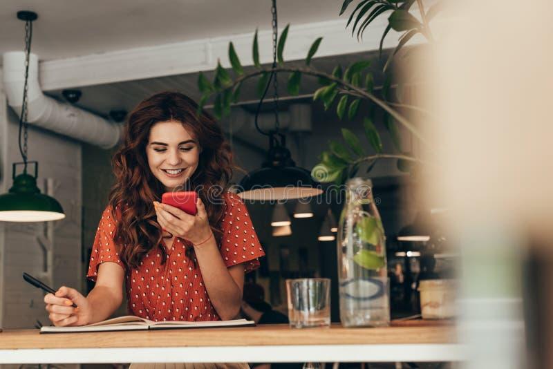 portrait du jeune blogger à l'aide du smartphone à la table avec le carnet photos libres de droits
