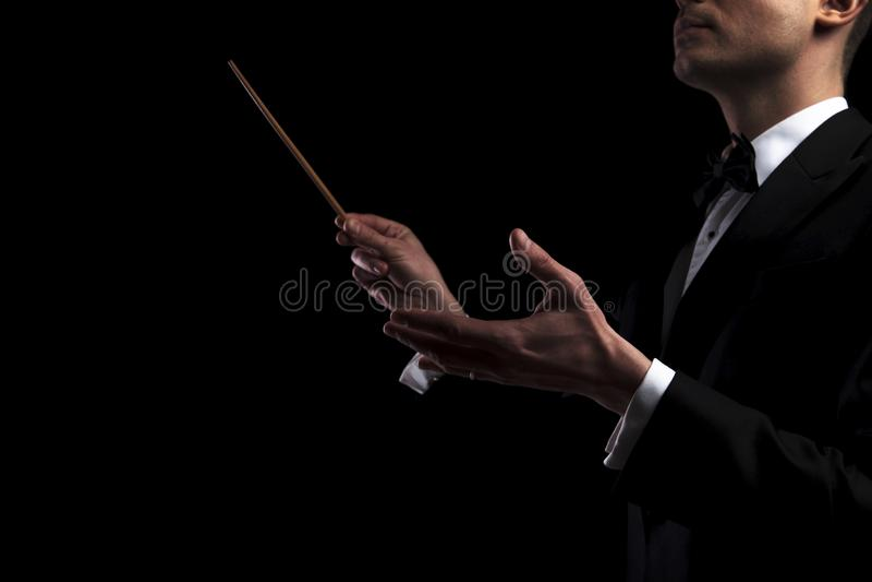 Portrait du jeune chef d'orchestre d'orchestre exécutant avec un bâton image libre de droits