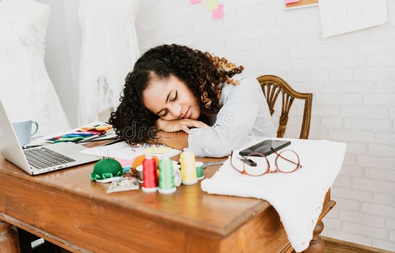 Portrait du jeune couturier fatigué de femme d'Afro-américain dormant tout en faisant des vêtements de conception dans l'ordinate image libre de droits