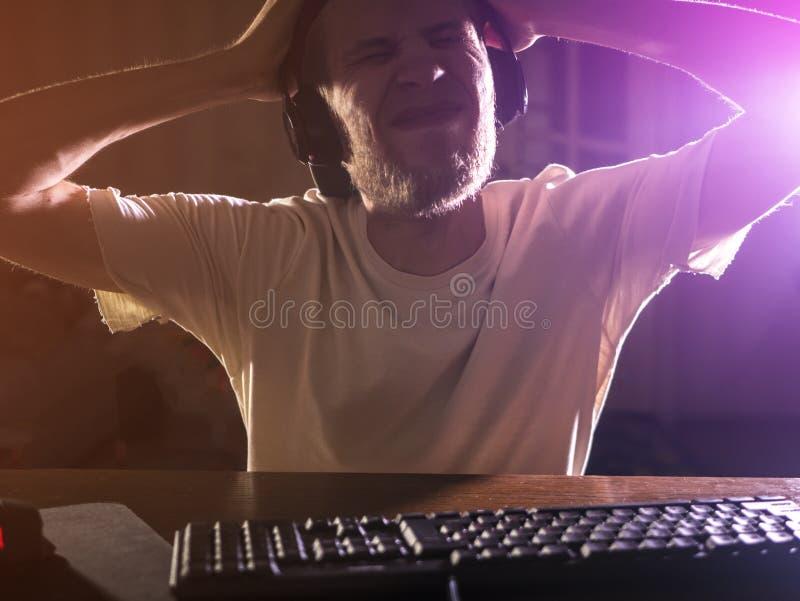 Portrait du jeune gamer masculin barbu jouant le jeu vidéo dans le fou devenant fou de nuit photo libre de droits