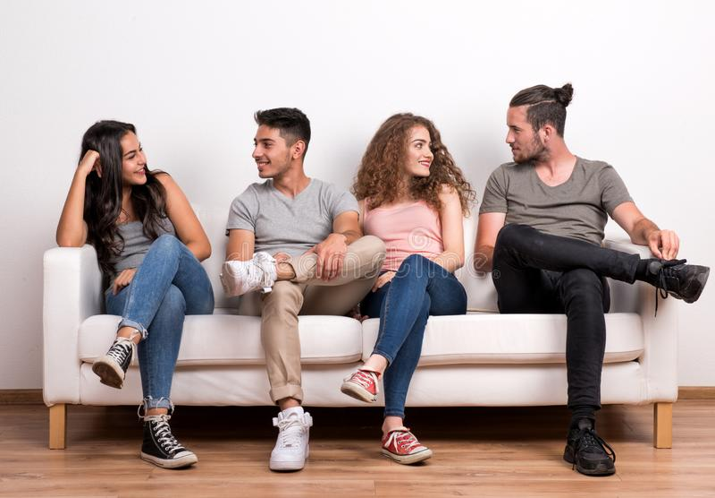 Portrait du jeune groupe d'amis s'asseyant sur un sofa dans un studio, parlant photographie stock