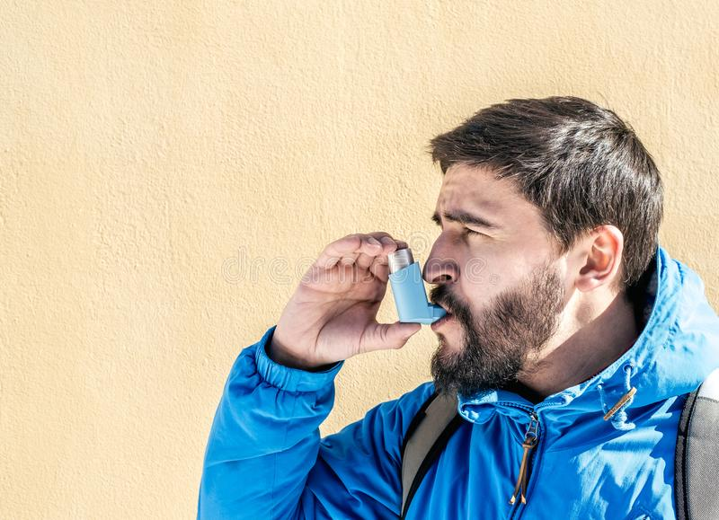 Portrait du jeune homme à l'aide de l'inhalateur d'asthme photo libre de droits