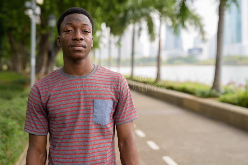 Portrait du jeune homme africain bel détendant au parc photo stock
