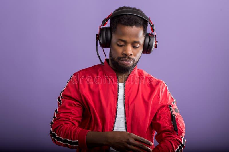 Portrait du jeune homme africain ?coutant la musique avec des ?couteurs photos stock