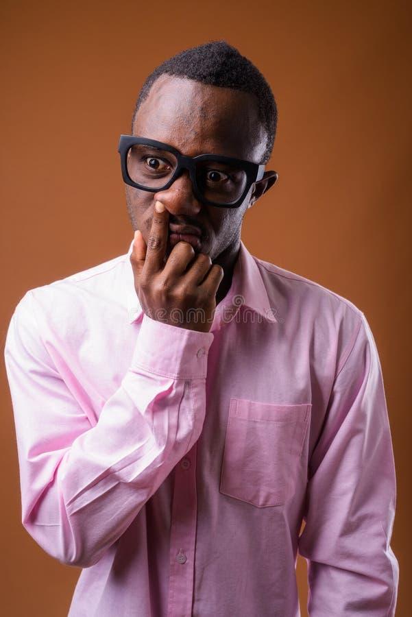 Portrait du jeune homme africain prenant son nez images stock