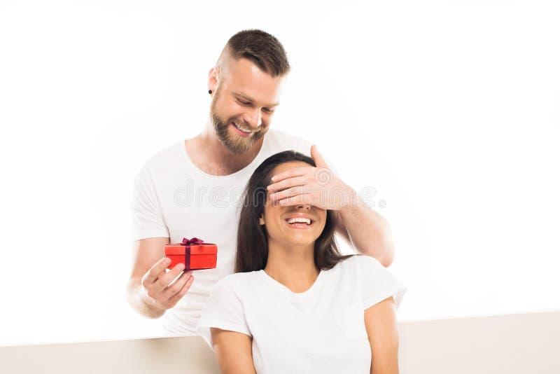 portrait du jeune homme attirant étonnant son amie par le cadeau, photos stock