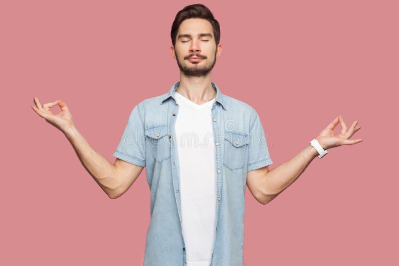 Portrait du jeune homme barbu beau d?contract? calme dans la position bleue de chemise de style occasionnel avec les bras augment photos stock