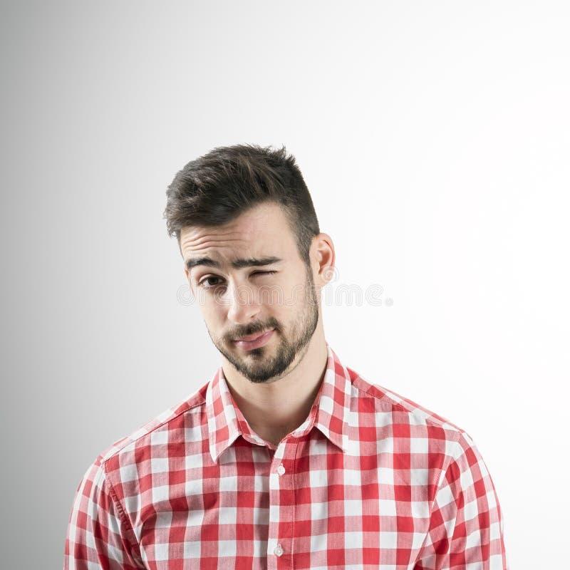 Portrait du jeune homme barbu clignant de l'oeil avec son oeil gauche photos stock