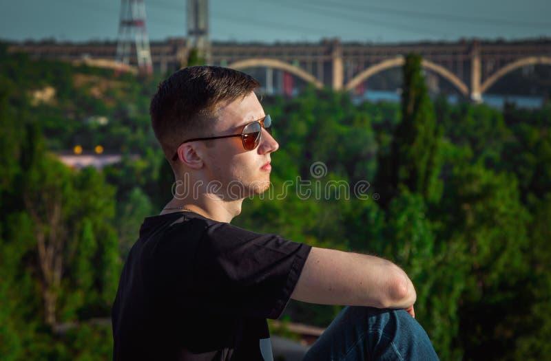 Portrait du jeune homme beau triste et songeur s'asseyant dehors photographie stock libre de droits