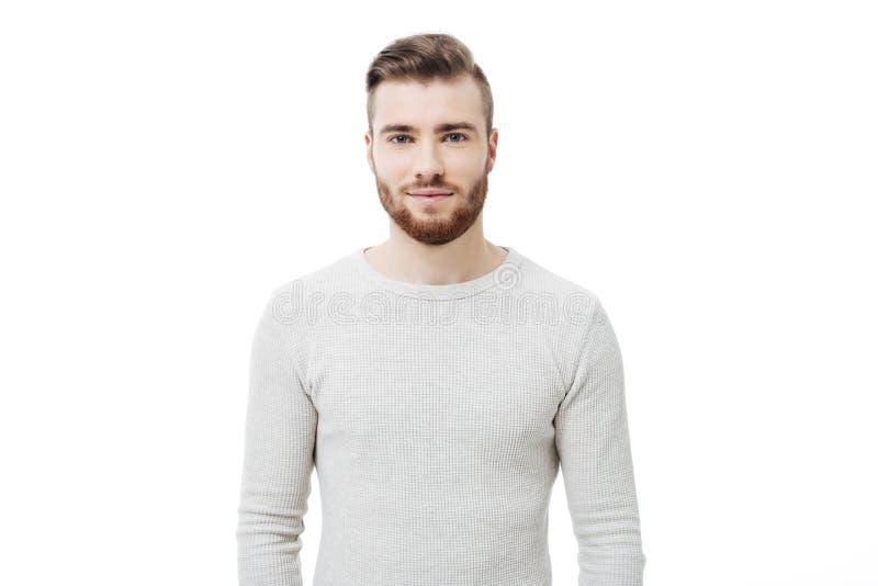 Portrait du jeune homme bel regardant l'appareil-photo au-dessus du fond blanc Type barbu attirant d'isolement photo stock