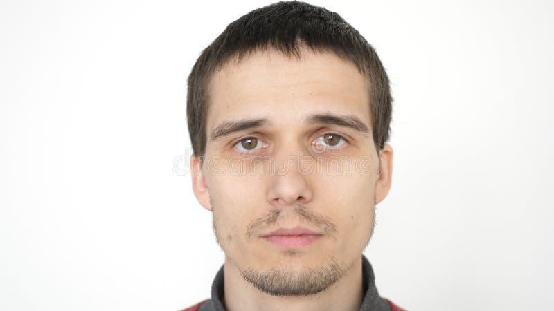 Portrait du jeune homme bouleversé attirant regardant la caméra sur un fond blanc photographie stock