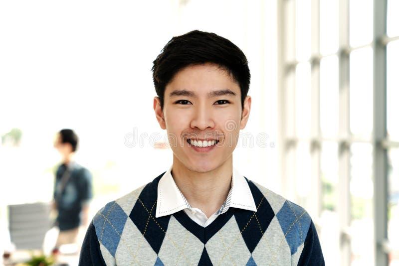 Portrait du jeune homme créatif asiatique attirant souriant et regardant l'appareil-photo image libre de droits