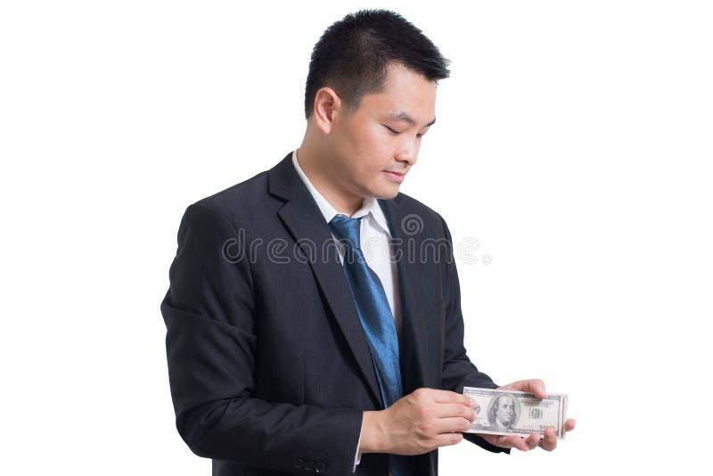 Portrait du jeune homme d'affaires asiatique sûr regardant au côté droit Mains comptant des billets de banque du dollar, photo stock