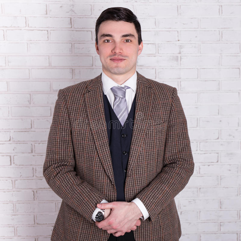 Portrait du jeune homme d'affaires bel posant au-dessus du mur blanc photo libre de droits