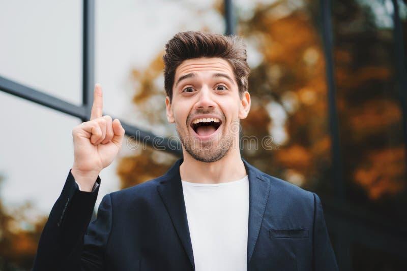 Portrait du jeune homme d'affaires considérant de pensée ayant le moment d'idée dirigeant le doigt sur le fond d'immeuble de bure image stock