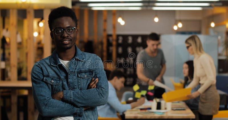 Portrait du jeune homme d'affaires réussi de sourire noir portant les lunettes élégantes se tenant dans le bureau moderne fonctio images stock
