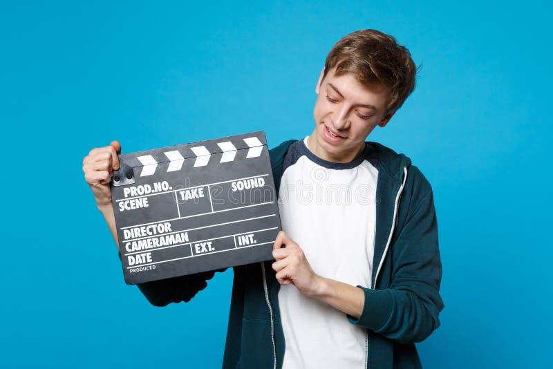 Portrait du jeune homme dans des vêtements sport tenant le regard sur la claquette noire classique de cinéma d'isolement sur le b photographie stock