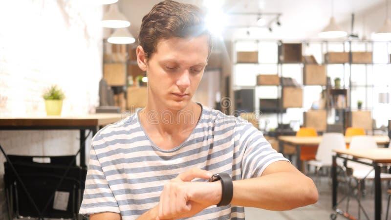 Portrait du jeune homme employant le smartwatch, photo libre de droits