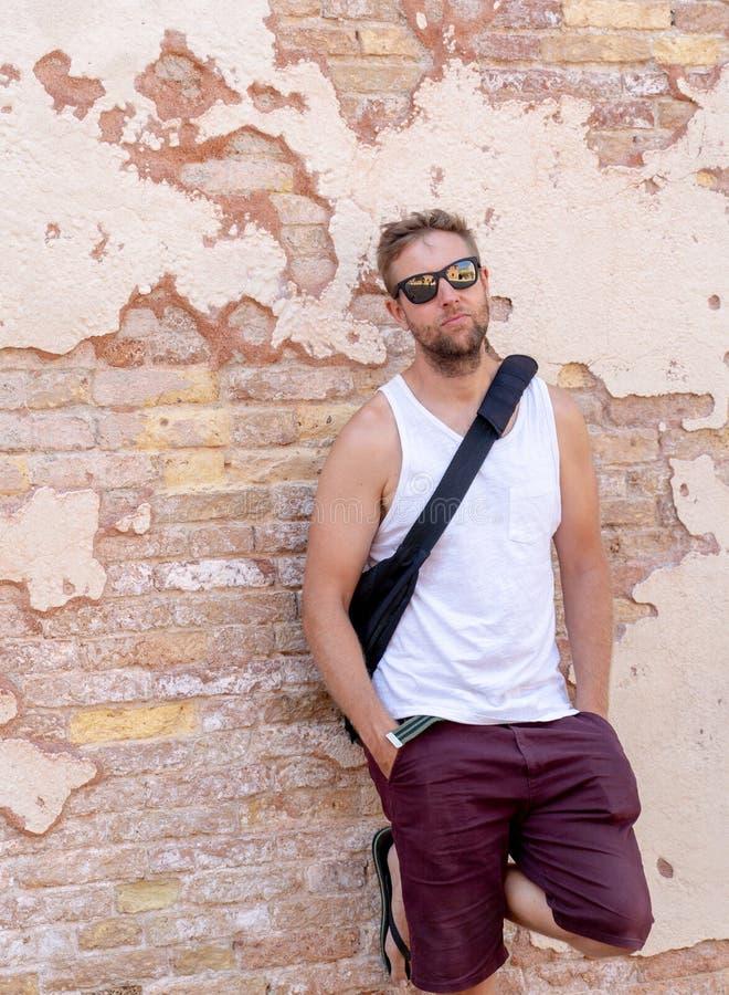 Portrait du jeune homme frais attirant se penchant sur le vieux mur de briques image stock