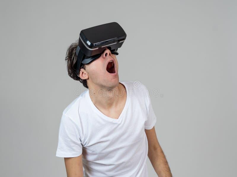 Portrait du jeune homme gai et choqu? utilisant le casque de 360 r?alit?s virtuelles explorant le monde 3D photo stock