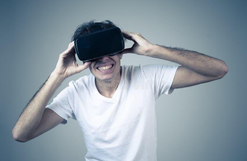 Portrait du jeune homme gai et choqu? utilisant le casque de 360 r?alit?s virtuelles explorant le monde 3D image stock