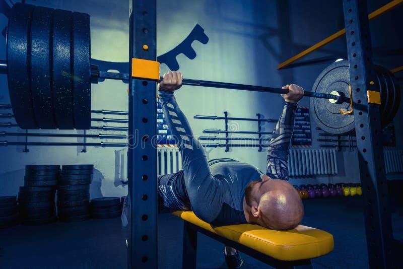 Portrait du jeune homme musculaire d'ajustement superbe établissant dans le gymnase avec le barbell images stock