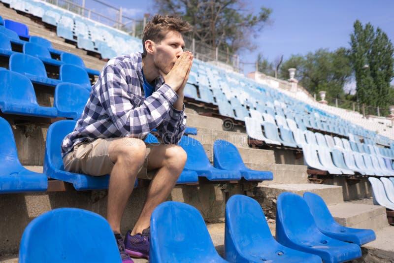 Portrait du jeune mâle émotif s'asseyant sur le stade de sport pendant les événements de match image libre de droits