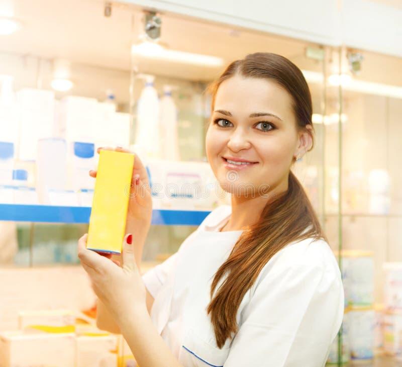 Portrait du jeune pharmacien féminin montrant la boîte de médecine photographie stock libre de droits