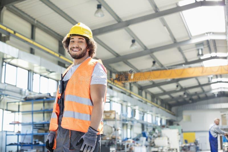 Portrait du jeune travailleur manuel de sourire se tenant dans l'usine photo stock