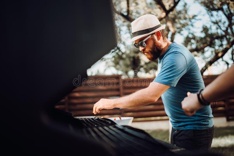 Portrait du jeune type ayant un gril de barbecue, faisant cuire la viande et des légumes photos libres de droits