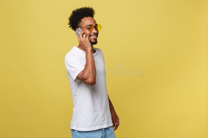 Portrait du jeune type noir frais parlant sur le téléphone portable D'isolement sur le fond jaune photographie stock