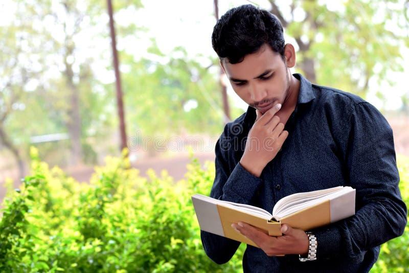 Portrait du livre de lecture heureux de jeune homme extérieur photographie stock