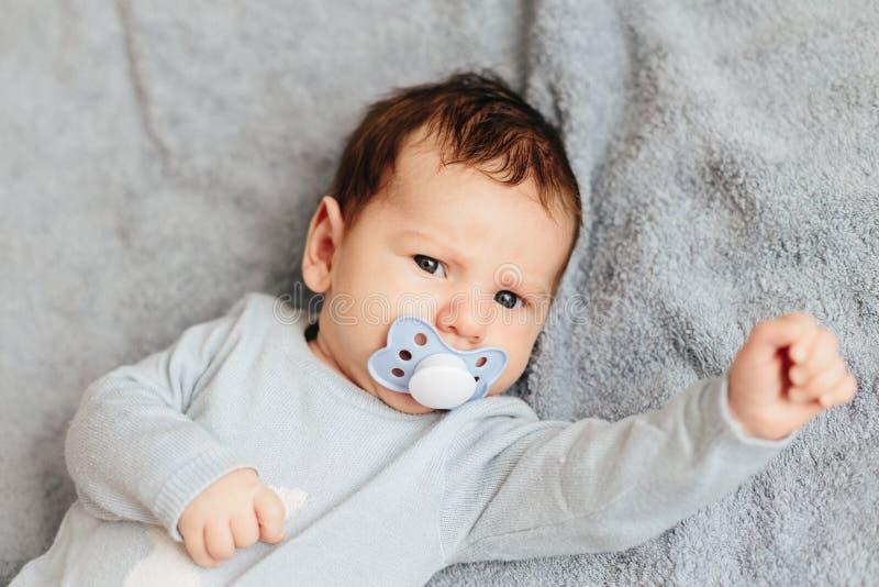 Portrait du mensonge fâché, furieux, fronçant les sourcils et agressif de bébé garçon sur un lit Les  photos libres de droits