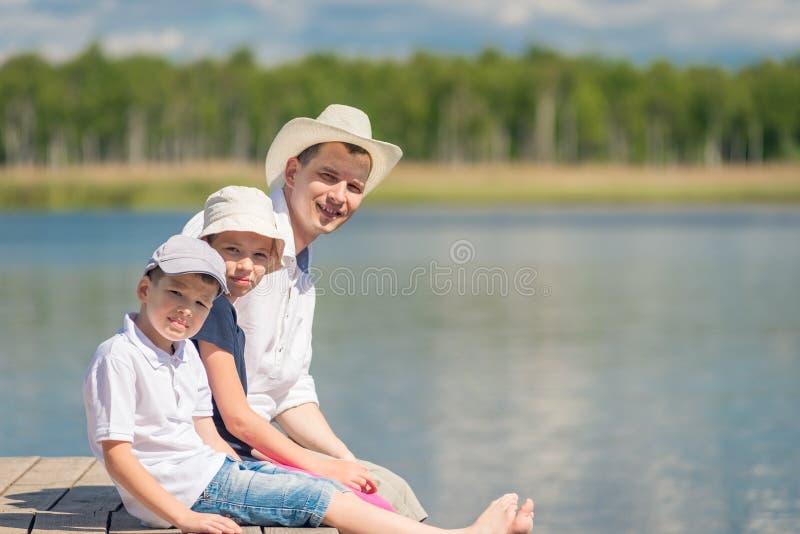 Portrait du père et des enfants s'asseyant sur un pilier en bois photographie stock libre de droits