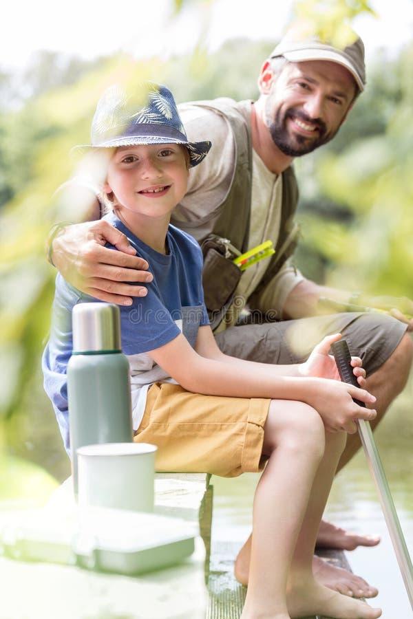 Portrait du père et du fils de sourire s'asseyant sur le pilier image libre de droits