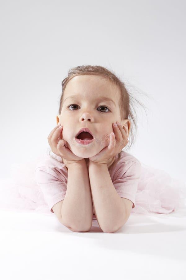 Portrait du petit enfant blond caucasien de baîllement posant dans le rose photographie stock
