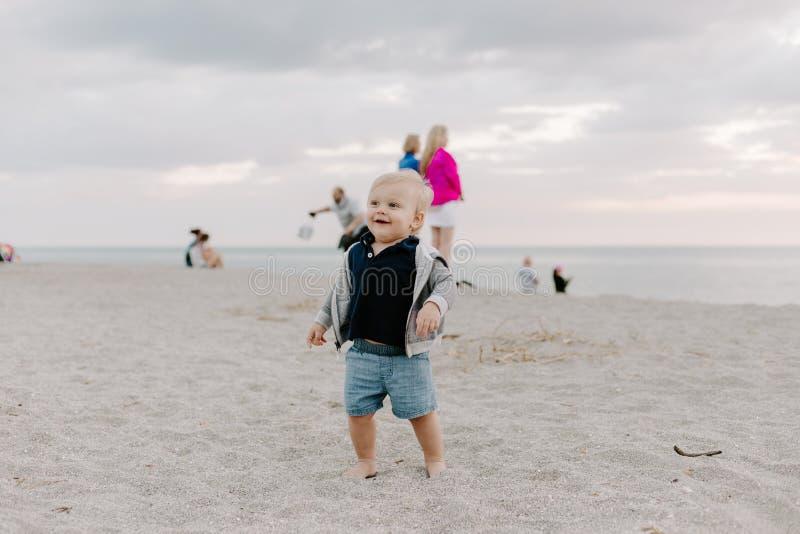 Portrait du petit enfant mignon de bébé garçon jouant et explorant dans le sable à la plage pendant l'extérieur de coucher du sol photo libre de droits