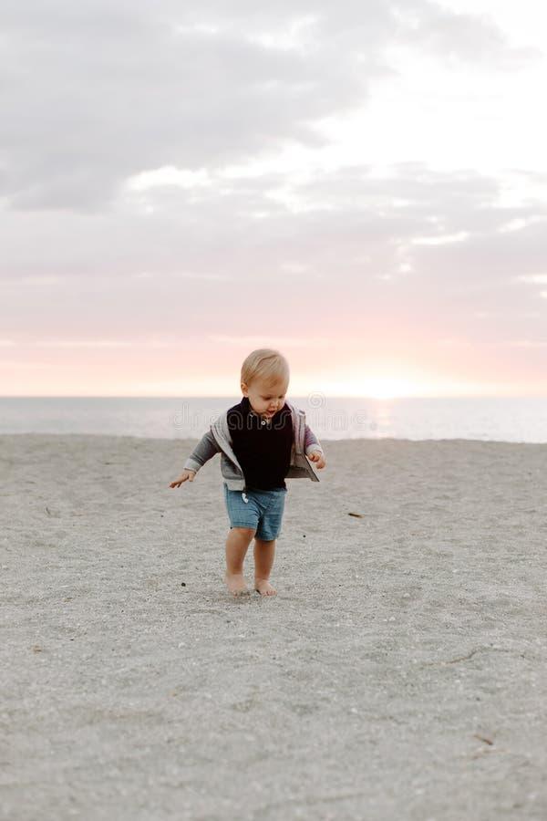 Portrait du petit enfant mignon de bébé garçon jouant et explorant dans le sable à la plage pendant l'extérieur de coucher du sol photographie stock