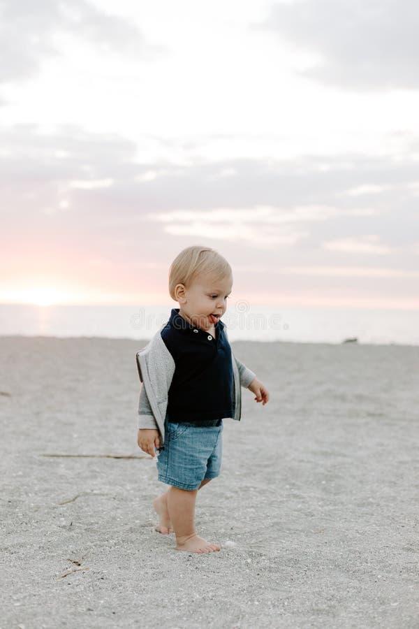 Portrait du petit enfant mignon de bébé garçon jouant et explorant dans le sable à la plage pendant l'extérieur de coucher du sol photo stock