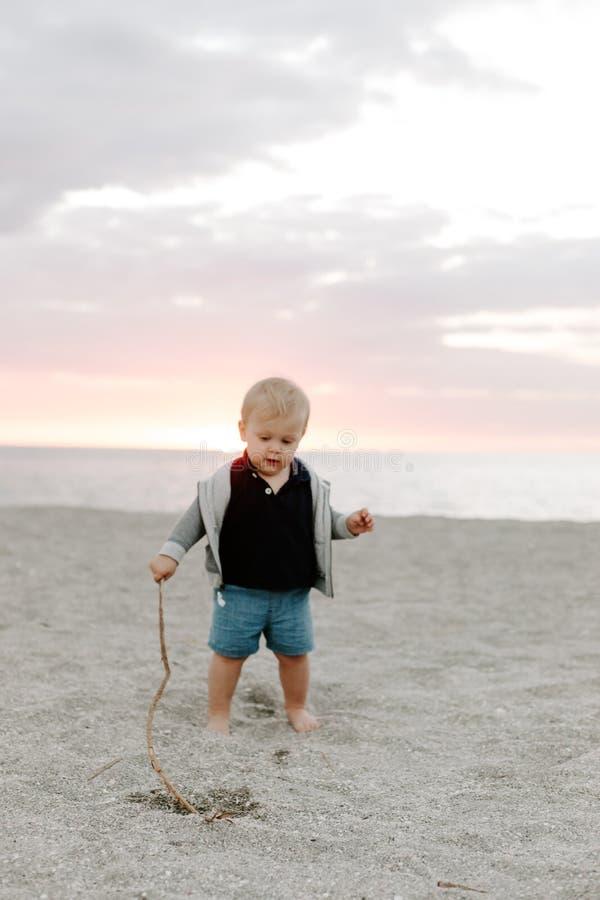 Portrait du petit enfant mignon de bébé garçon jouant et explorant dans le sable à la plage pendant l'extérieur de coucher du sol photos stock