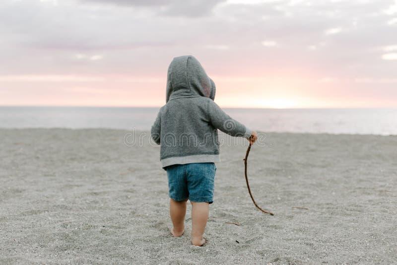 Portrait du petit enfant mignon de bébé garçon jouant et explorant dans le sable à la plage pendant l'extérieur de coucher du sol photos libres de droits