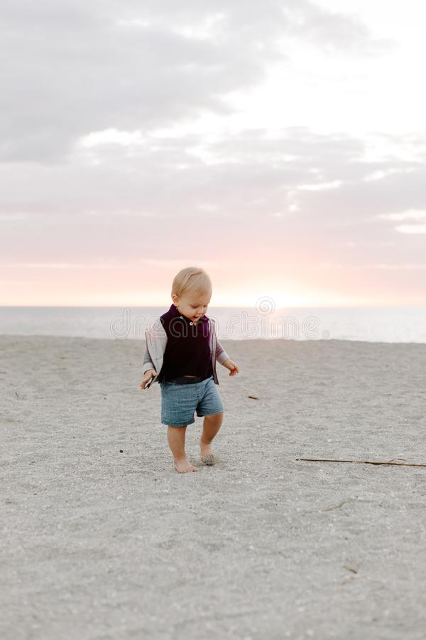 Portrait du petit enfant mignon de bébé garçon jouant et explorant dans le sable à la plage pendant l'extérieur de coucher du sol images libres de droits