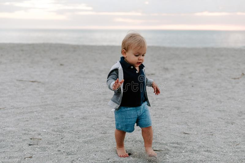 Portrait du petit enfant mignon de bébé garçon jouant et explorant dans le sable à la plage pendant l'extérieur de coucher du sol image stock