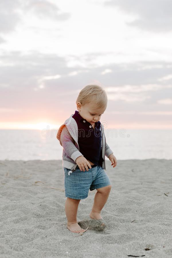 Portrait du petit enfant mignon de bébé garçon jouant et explorant dans le sable à la plage pendant l'extérieur de coucher du sol images stock