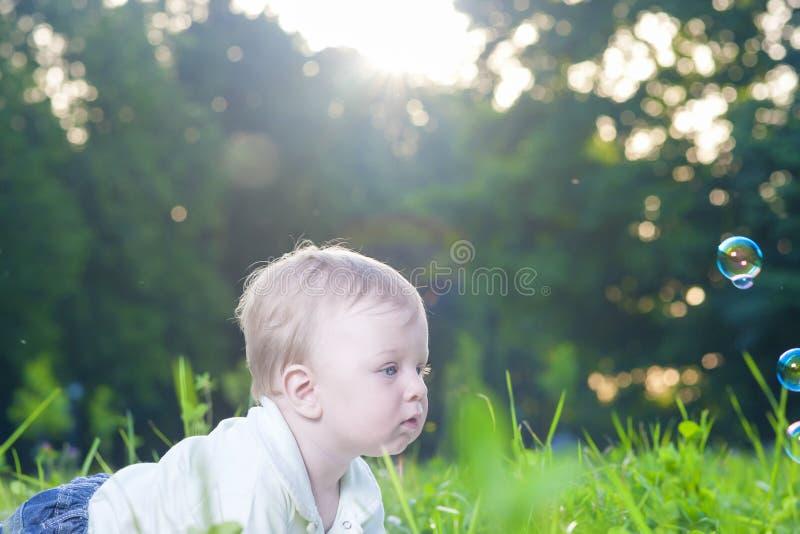 Portrait du petit garçon caucasien mignon jouant avec des bulles de savon image libre de droits