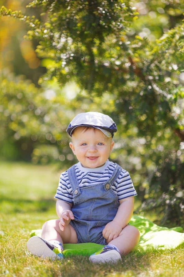 Portrait du petit garçon mignon s'asseyant sur l'herbe image libre de droits