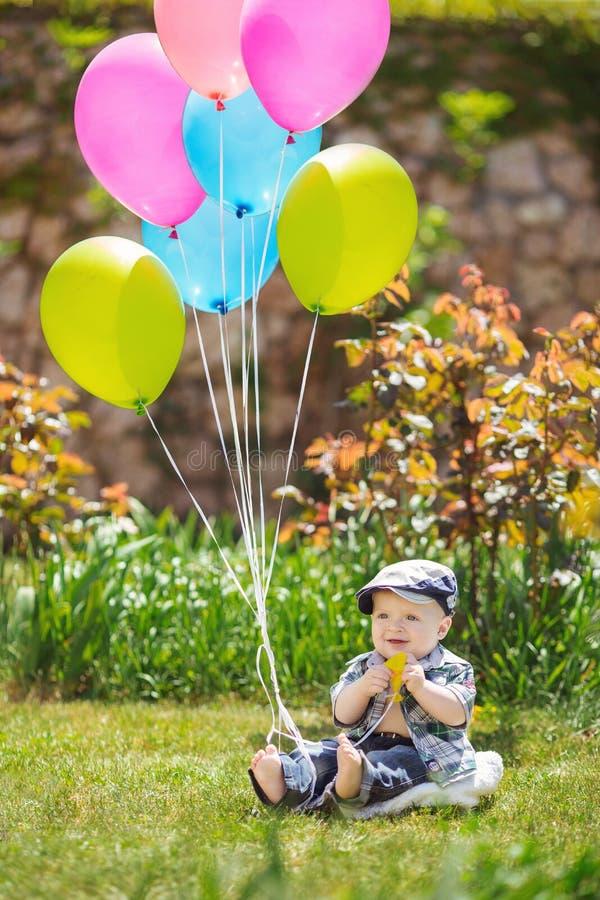 Portrait du petit garçon mignon s'asseyant sur l'herbe image stock