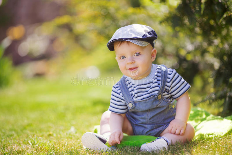 Portrait du petit garçon mignon s'asseyant sur l'herbe photographie stock
