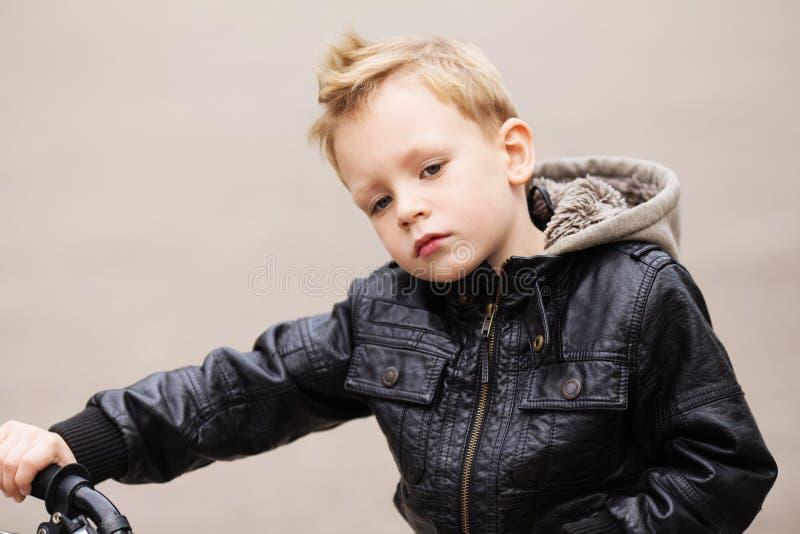 Portrait du petit garçon urbain adorable portant le cric en cuir noir image stock